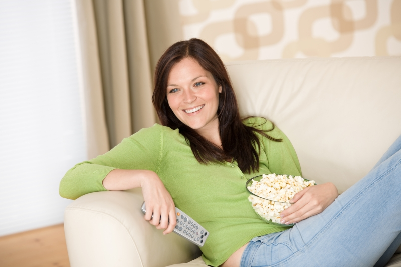 1609949-woman-pointing-with-television-remote-control